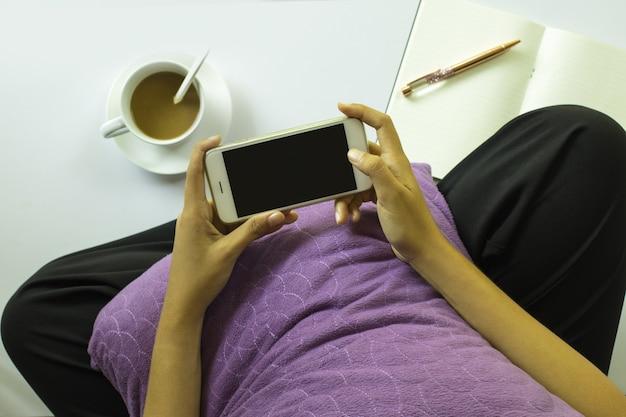 白い背景にスマートフォンとコーヒーのカップの写真を撮る女性。上面図。