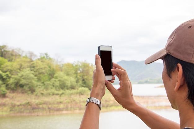 スマートフォンを使って写真を撮る男