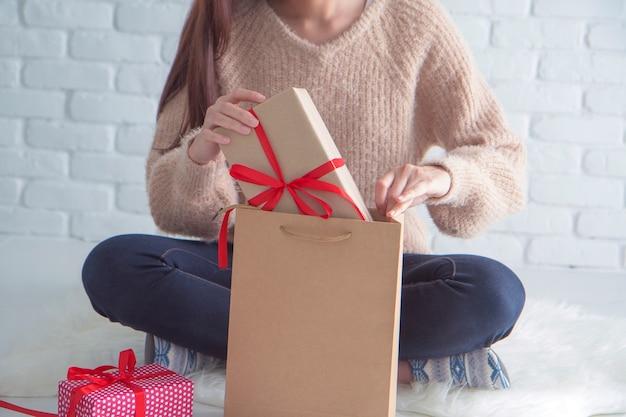 茶色の紙袋の贈り物箱を開く茶色のセーターの若い女性。
