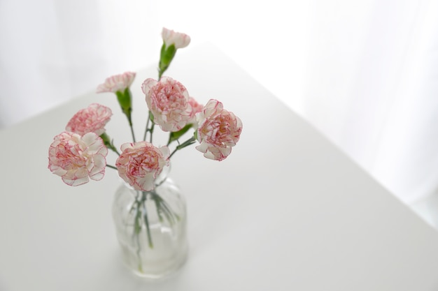 ホワイトルームの白いテーブルにピンクと白のカーネーション花の花瓶のトップビュー。