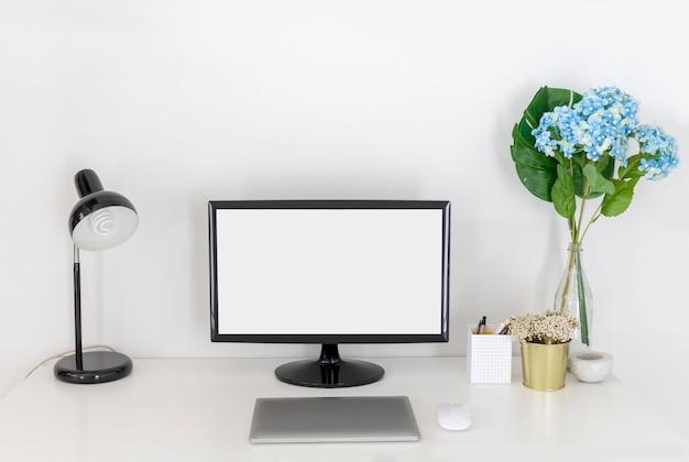 Пустой экран пк и ноутбук с канцелярскими принадлежностями на белом рабочем столе.