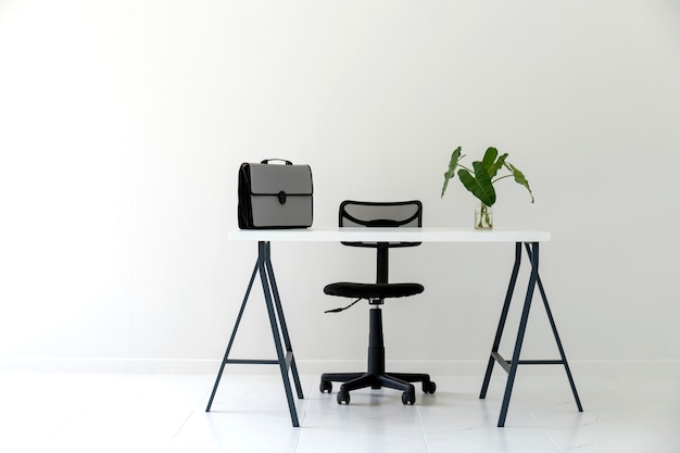白いテーブル、黒い椅子、ドキュメントバッグ付きの近代的な白いオフィスのインテリア