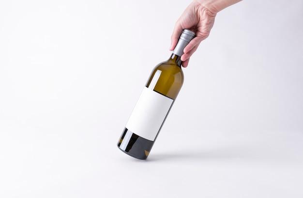 モックアップのためのワインの瓶を持っている手。灰色の背景上の空白のラベル。