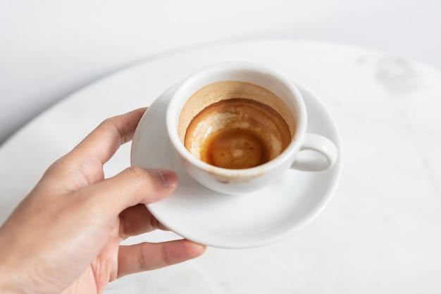 カフェのテーブルにエスプレッソコーヒーカップ平面図を持っている手。