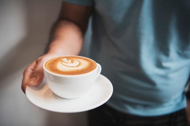 カフェで泡状の泡、コーヒーカップ上面とラテやカプチーノを持っている手。