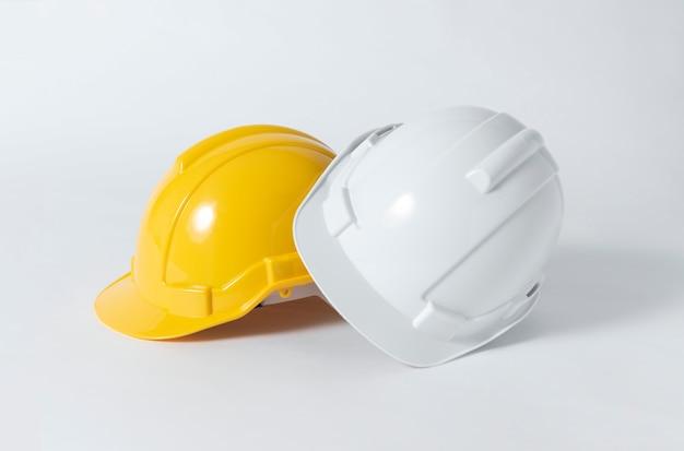 灰色の背景上のエンジニアのためのプラスチック製の安全ヘルメット。