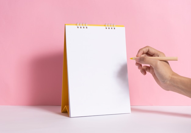 ピンクの背景のモックアップ紙スパイラルカレンダーにマーキングを書くための手持ち株鉛筆。