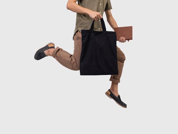 Человек прыжок держит мешок холст ткани для макета пустой шаблон.