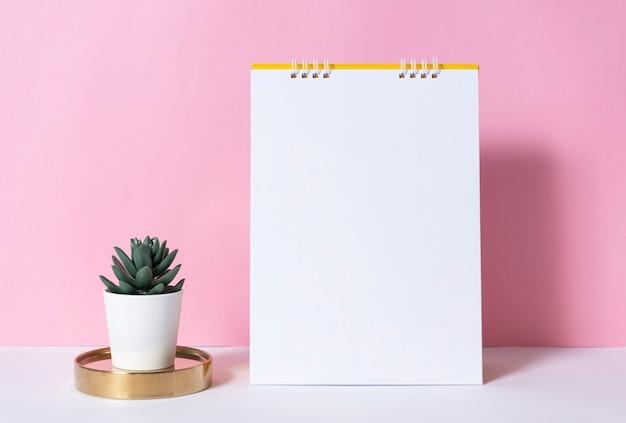 ピンクの背景のサボテンとモックアップ紙スパイラルカレンダー。