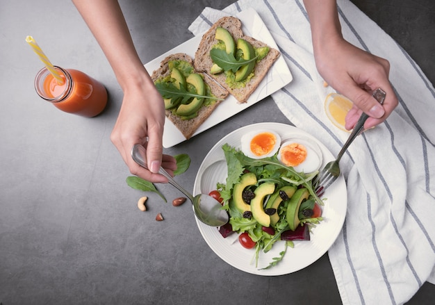 テーブルの上の皿に卵、トマト、アボカド、ほうれん草、レタスの新鮮な健康野菜サラダ。