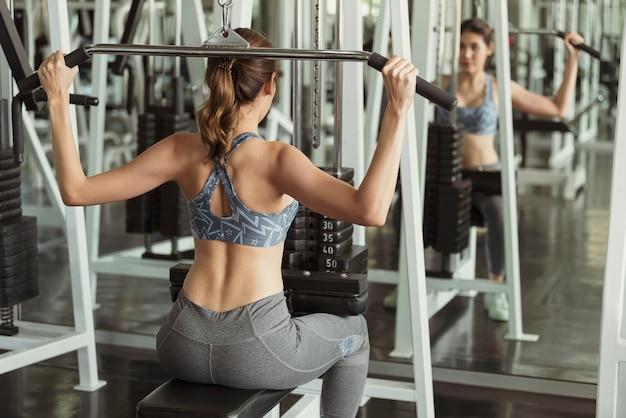 若いアジア女性がジムでバーベルを持ち上げます。健康的なライフスタイルとトレーニングの動機の概念。