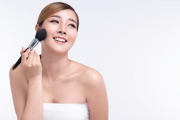 美容化粧品の赤面を持っている手で完璧な顔の肌を持つ若いアジア女性。広告美容のためのジェスチャー。
