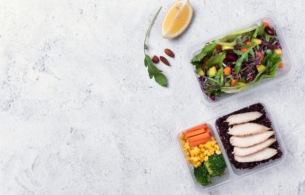 ダイエットメニューのフリーテキストスペースを持つ表の背景に野菜サラダと新鮮な健康的なダイエットランチボックス。