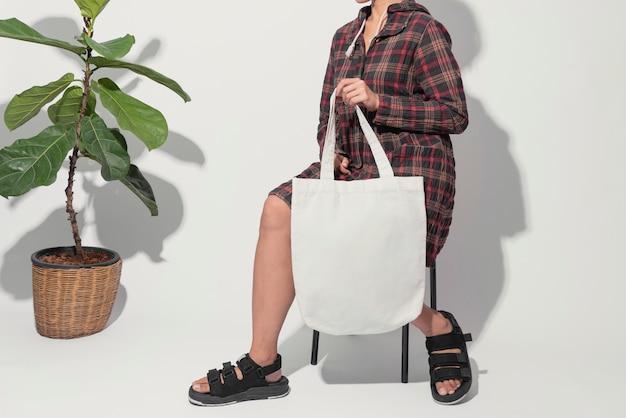 Девушка держит сумку холст ткани.