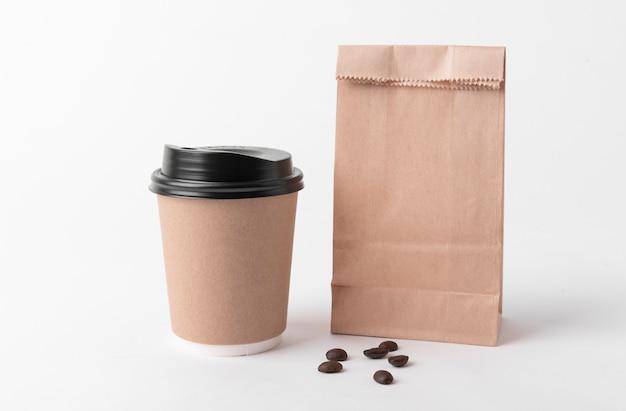 Пустой коричневый бумажный пакет и чашка кофе
