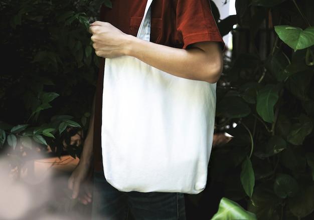 男はバッグキャンバス生地を保持しています。