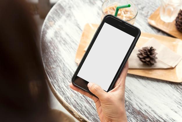 カフェの木製テーブルに空白の画面を持つ携帯電話を使用して保持している手のモックアップ画像。