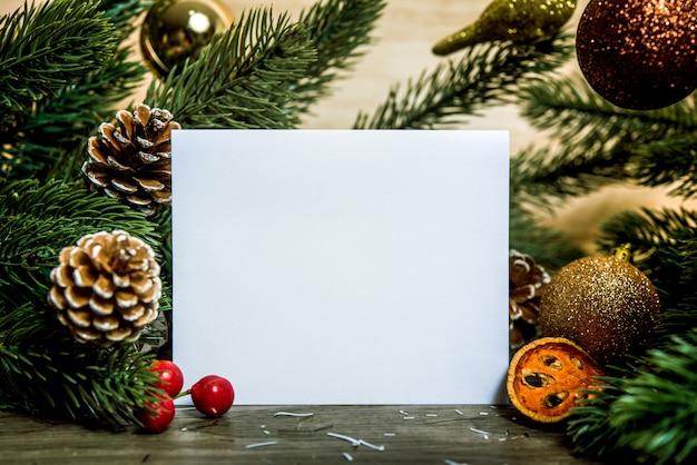 Макет дизайна бумажной карточки поздравительной открытки праздника рождества с украшением на деревянной таблице.