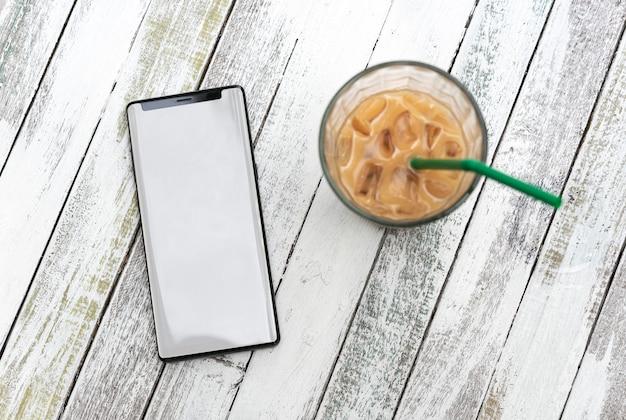 空白の画面とカフェの木製テーブルの上のコーヒーカップを持つ携帯電話。
