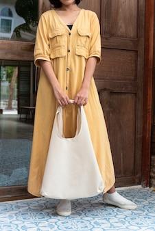 Девушка держит сумку холст ткани