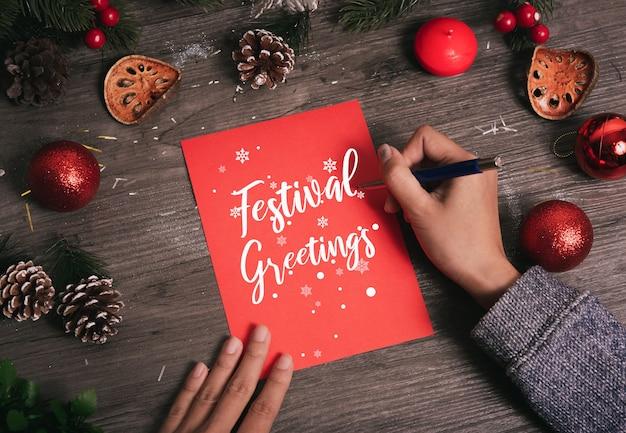 手書きグリーティングカード木製のテーブルにクリスマスの装飾とメリークリスマスのテキスト。