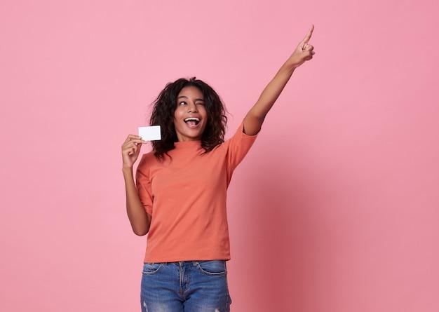 ピンクの背景に指している彼女の指で立っている幸せな若いアフリカ人女性