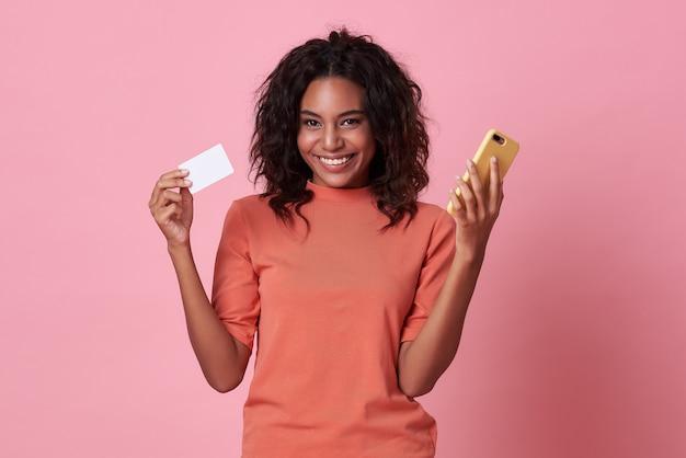 ピンクの背景にクレジットカードと携帯電話を示す若いアフリカ人女性