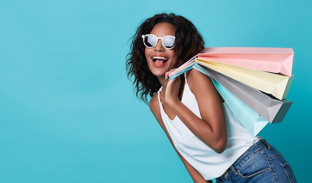 買い物袋を保持している興奮した若いアフリカ人女性