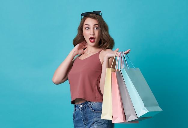 Взволнованная молодая женщина, держащая сумки