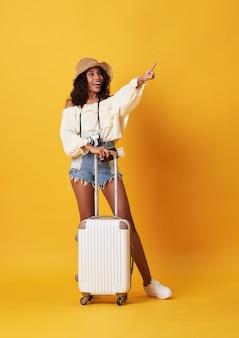 Веселая молодая африканская женщина, одетая в летнюю одежду, стоя с чемоданом