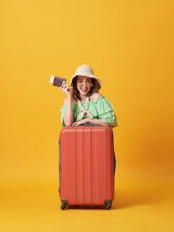 お金でパスポートを保持している夏服に身を包んだ陽気な若い女性