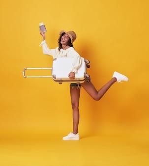 Веселая молодая негритянка в летней одежде держит чемодан и паспорт и работает