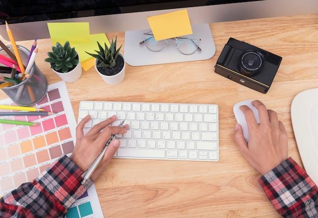 Художник-график руки печатает на клавиатуре компьютера на деревянном столе