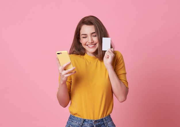 ピンクで分離された携帯電話とクレジットカードを保持している幸せな若い女性の肖像画。