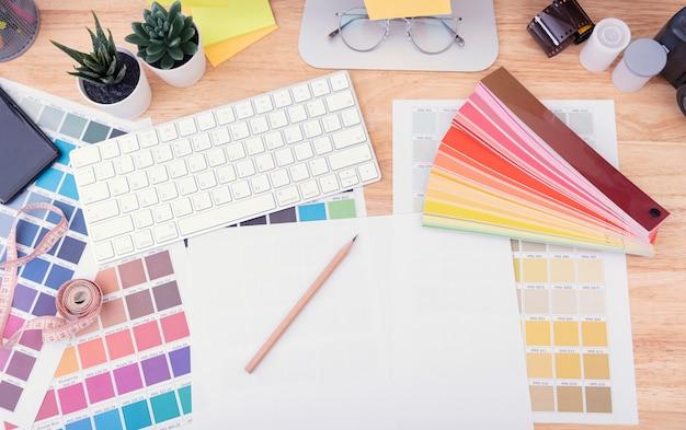 グラフィックデザイナーアーティストが紙に描くための機器とオフィスのデスクで彼の仕事をカラーチャートします。