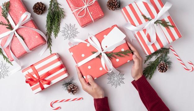 クリスマスの日に人々に与える赤いギフトボックスを持っている手。休日のお祝いと新年あけましておめでとうございますコンセプト。