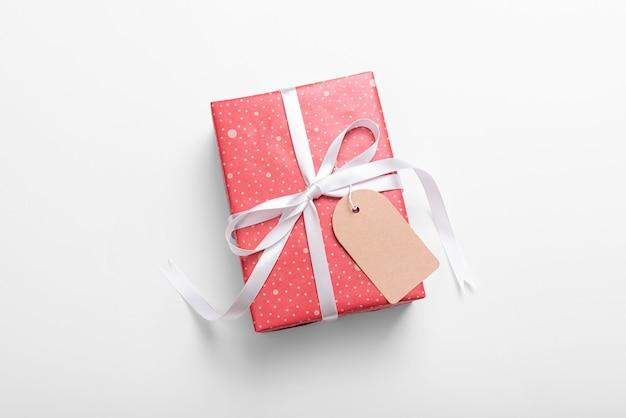 Красная бирка подарочной коробки и бумаги изолированная на белизне на рождество и.