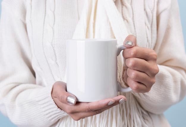 白いセラミックコーヒーカップを持つ女性の手。創造的な広告テキストメッセージまたはプロモーションコンテンツのモックアップ。