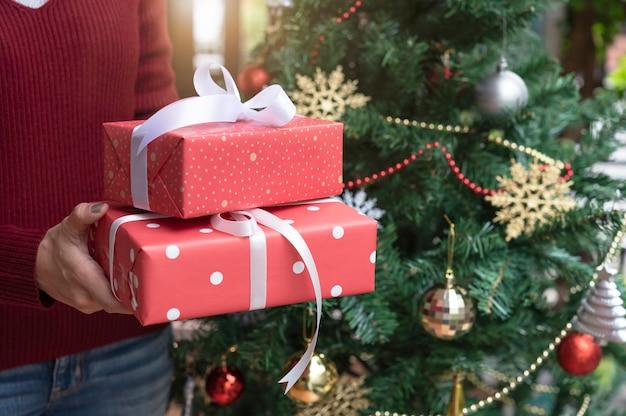 Женщины вручают держать красную подарочную коробку на предпосылке рождественской елки для концепции рождества и нового года.