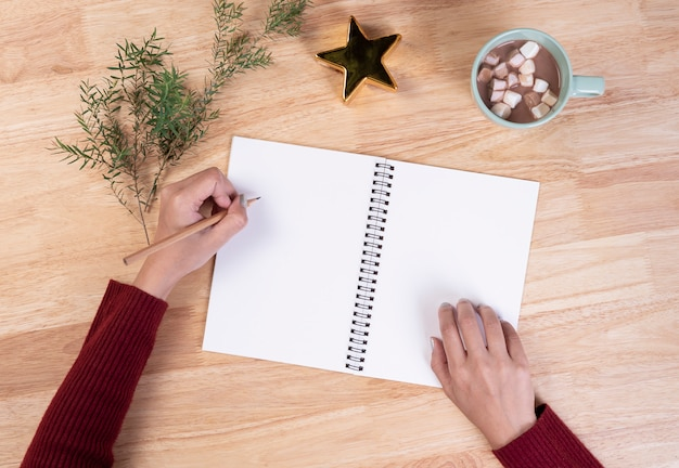 手書きのリストと木製の背景にマシュマロとホットチョコレートのモックアップはがきを書きます。冬のクリスマスと新年あけましておめでとうございますコンセプト。