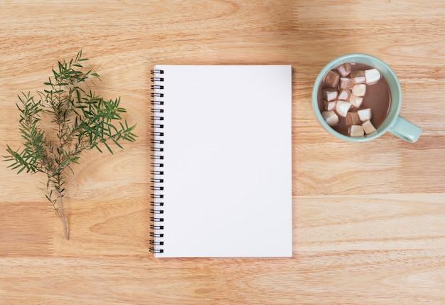 木製の背景にマシュマロとリストとホットチョコレートを行うためのモックアップはがき。冬のクリスマスと新年あけましておめでとうございますコンセプト。