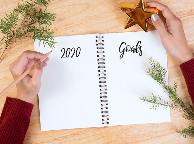 木製テーブルの上のリストを行う目標の手書きのモックアップ