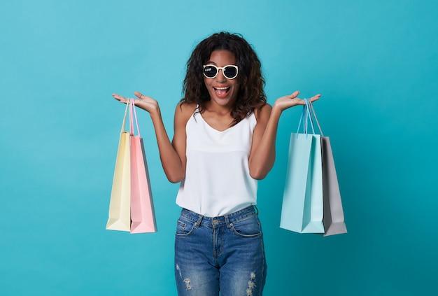 青い背景に分離された買い物袋を持っている幸せの美しい若い女性の手。