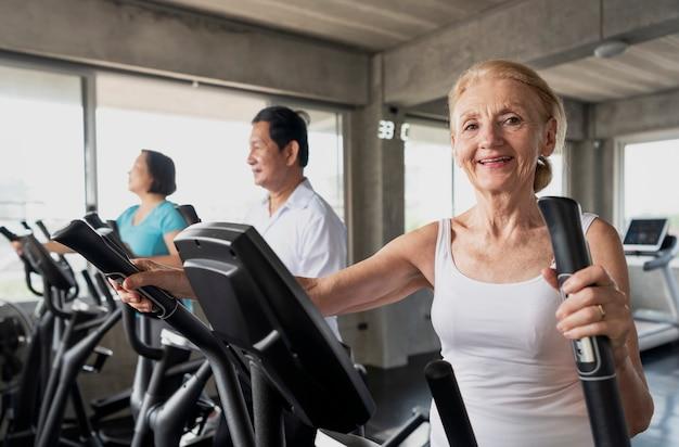 年配の女性がフィットネスジムでスピニングバイクを行使します。高齢者の健康的なライフスタイルのコンセプト。