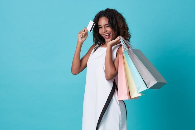 買い物袋とクレジットカードを保持している白いドレスの若いアフリカ人女性
