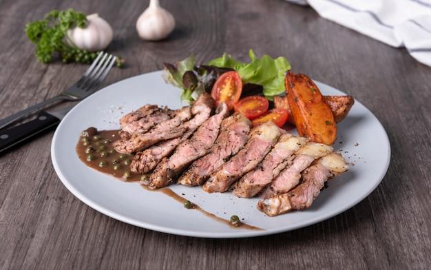 テーブルレストランの白い皿にビーフステーキと野菜のサラダとポテトチップス。上面図。