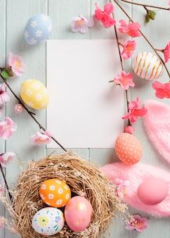 Счастливая пасха, бумажная карточка и покрашенные пасхальные яйца в гнезде на деревянном столе. вид сверху с копией пространства.