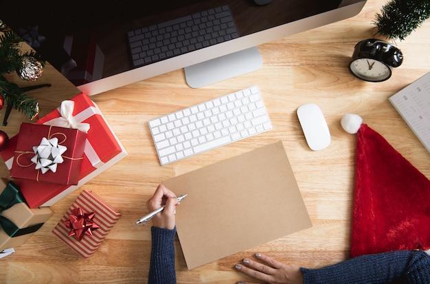 木製テーブルの上の装飾と幸せな新年休日グリーティングカードデザインモックアップ。