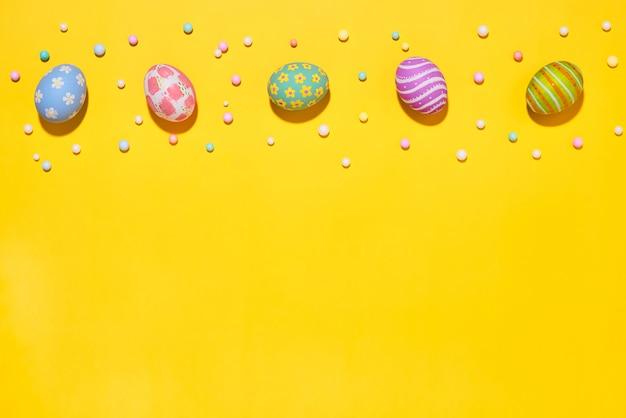 創造的なイースターホリデーレイアウトの卵は、黄色の背景にリボン泡パーティーと手作りペイントエドを着色しました。季節のフラットレイアウトコンセプト。