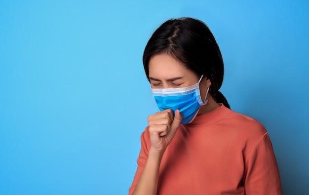 インフルエンザで咳をしながらくしゃみをして口と鼻を覆っている女性。流行性コロナウイルス防御。